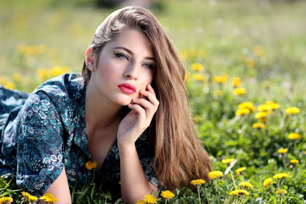 An image of a beautiful girl in a field with healthy radiant skin through skin care