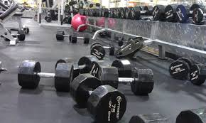 An image of a messy gym, with weights all over the place.