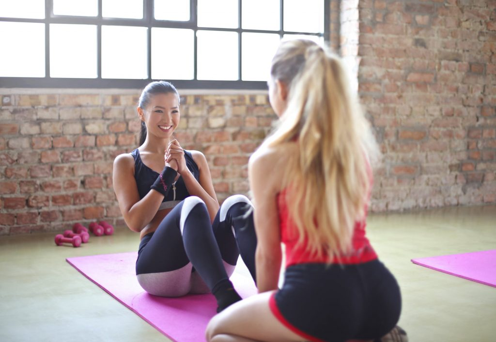 An image of two fit girls practicing yoga