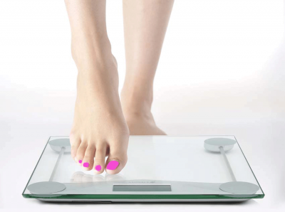 Woman stepping on bathroom scales barefoot
