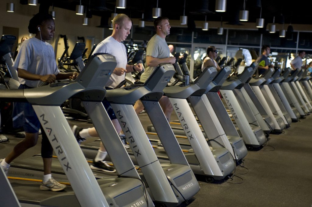 An image of people running on treadmills at the gym.