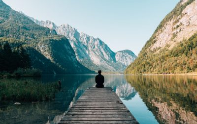 A picture of a man reflecting upon a lake